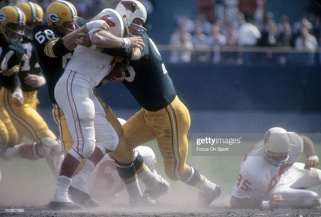 BAY, WI - CIRCA 1960's: Linebacker Ray Nitschke #66 of the Green Bay Packers gets a hand on running back John David Crow #44 of the St. Louis Cardinals during a circa mid 1960's NFL football game at Lambeau Field in Green Bay, Wisconsin. Nitschke played for the Packers from 1958-72.