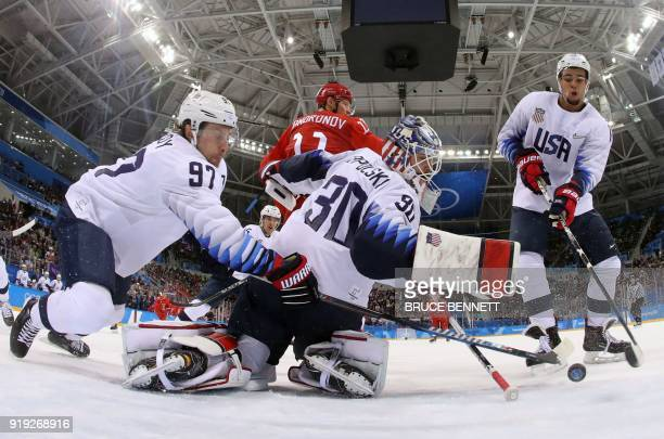 S Matt Gilroy , Ryan Zapolski and Jordan Greenway reach for the puck in the men's preliminary round ice hockey match between the US and Olympic...