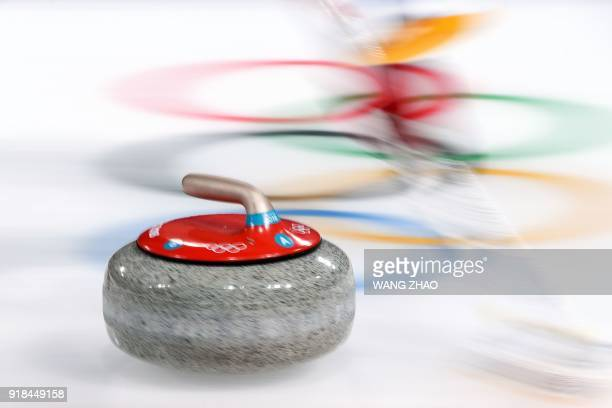 S Matt Hamilton brushes in front of the stone during the curling men's round robin session between the US and Italy during the Pyeongchang 2018...
