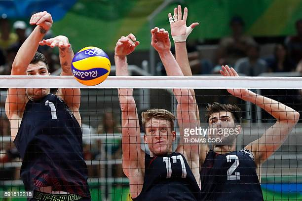 USA's Matthew Anderson USA's Maxwell Holt and USA's Aaron Russell jump up to block the ball during the men's quarterfinal volleyball match between...