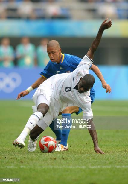 S Maurice Edu and Japan's Takayuki Morimoto battle for the ball