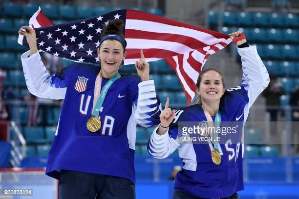 TOPSHOT USA's Megan Keller holds the US flag with teammate Danielle Cameranesi after the medal ceremony after winning the women's ice hockey event...