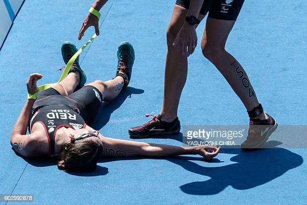 UK's Melissa Reid falls besides her guide Nicole Walters at the goal during women's triathlon of the Rio 2016 Paralympic Games at Copacabana beach in...