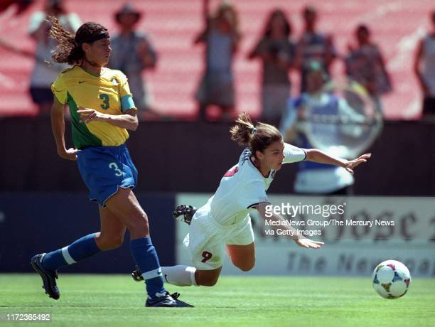 S Mia Hamm, right, goes flying after being fouled by Brazil's Elane, which gave the US a penalty kick. US defender Michelle Akers scored on the...