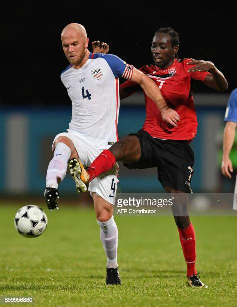 USA's Michael Bradley and Trinidad and Tobago's Nathan Lewis vie for the ball during their 2018 World Cup qualifier football match in Couva Trinidad...