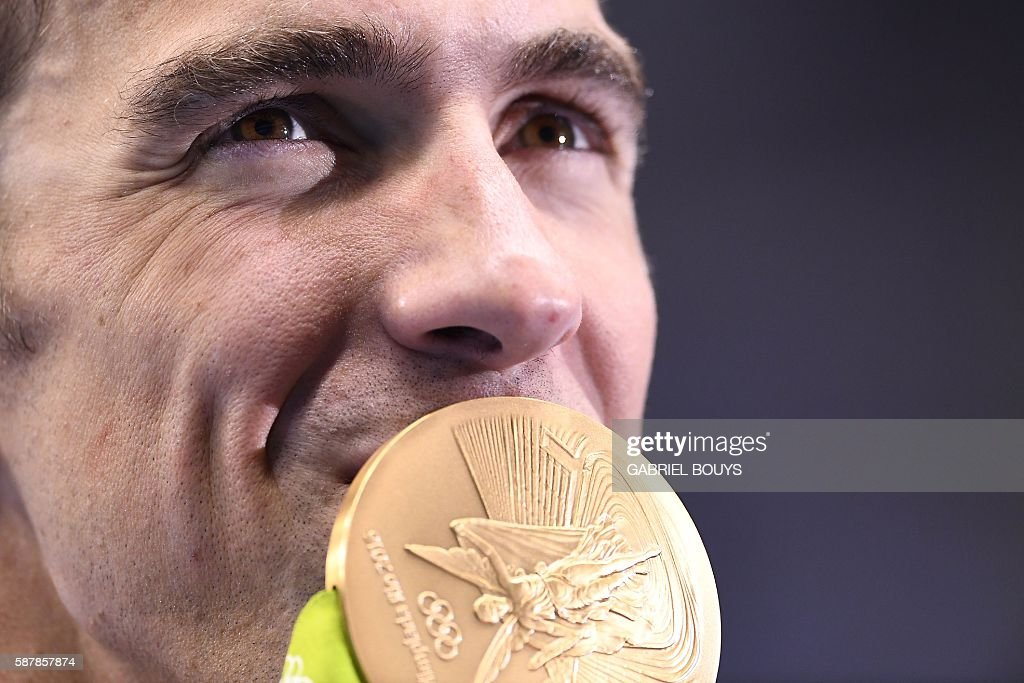 TOPSHOT - USA's Michael Phelps kisses his gold medal on the podium after Team USA won the Men's 4x200m Freestyle Relay Final during the swimming event at the Rio 2016 Olympic Games at the Olympic Aquatics Stadium in Rio de Janeiro on August 9, 2016. / AFP / GABRIEL
