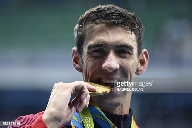 S Michael Phelps kisses his gold medal on the podium after Team USA won the Men's 4x200m Freestyle Relay Final during the swimming event at the Rio...