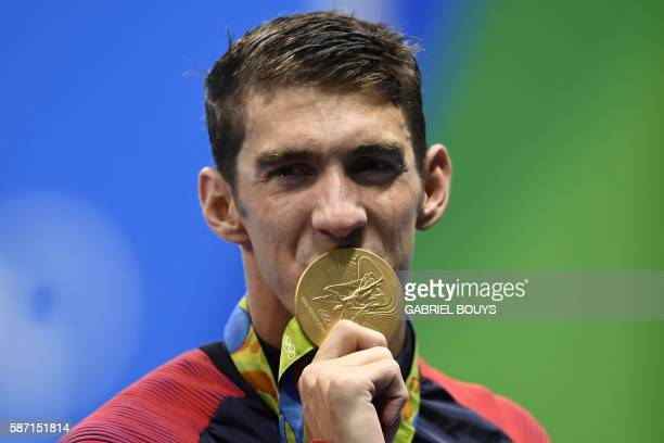 S Michael Phelps kisses his gold medal on the podium of the Men's 4x100m Freestyle Relay Final during the swimming event at the Rio 2016 Olympic...