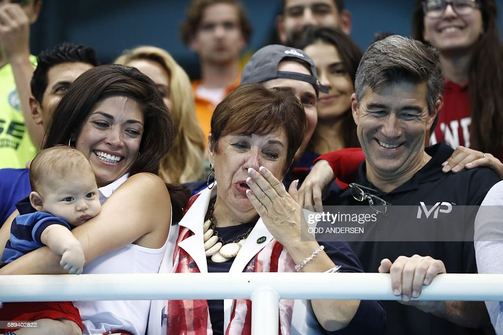 TOPSHOT - USA's Michael Phelps' mother Deborah (C) and partner Nicole Johnson (L) holding Michael Phelps' son, Boomer celebrate after the Men's swimming 4 x 100m Medley Relay Final at the Rio 2016 Olympic Games at the Olympic Aquatics Stadium in Rio de Janeiro on August 13, 2016. / AFP / Odd ANDERSEN