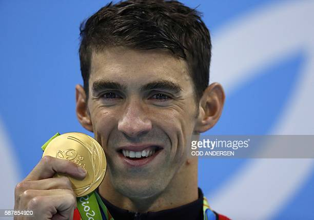TOPSHOT USA's Michael Phelps poses on the podium with his gold medal after he won the Men's 200m Butterfly Final during the swimming event at the Rio...