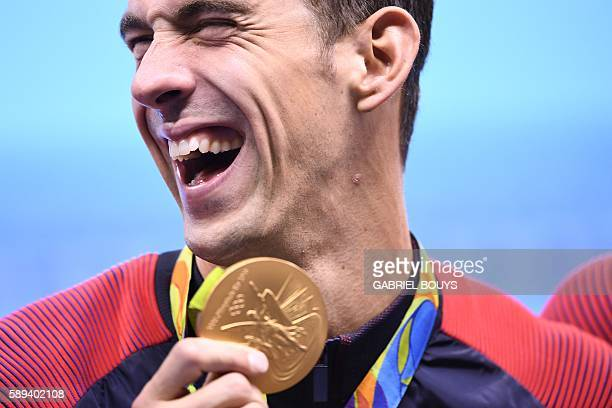 TOPSHOT USA's Michael Phelps poses with his gold medal during the podium ceremony of the Men's swimming 4 x 100m Medley Relay Final at the Rio 2016...