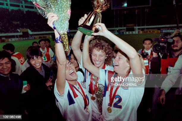 US's Michelle AkersStahl and her teammates Julie Foudy and Carin Jennings celebrate their 21 victory over Norway in their final match at first FIFA...