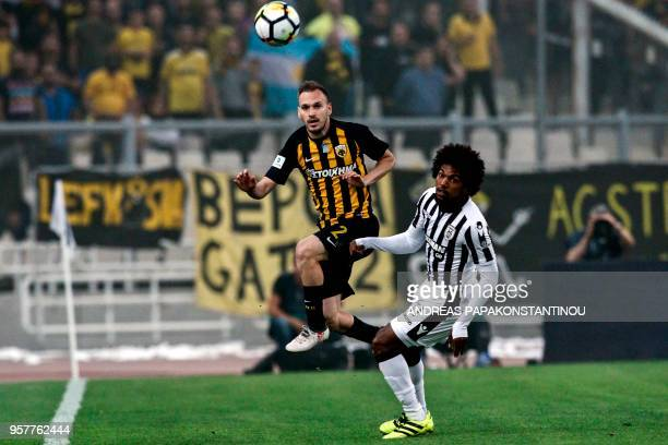 AEK's Mihalis Bakakis vies for the ball with PAOK's Salonika Diego Biseswar during the Greek Cup final football match between AEK FC and PAOK...