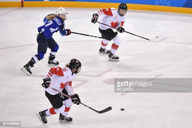 USA's Monique LamoureuxMorando fights for the puck with Canada's Emily Clark and Jocelyne Larocque in the women's gold medal ice hockey match between...