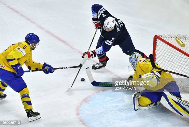 US's Nick Bonino vies with Sweden's Mikael Wikstrand and Sweden's goalie Anders Nilsson during the semifinal match Sweden vs USA of the 2018 IIHF Ice...