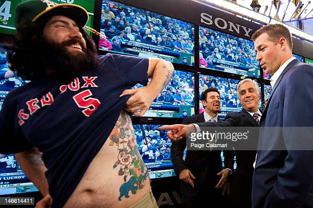 ESPN's Nomar Garciaparra Pedro Gomez and Mark Mulder check out Cave Dweller Benjamin Christensen's mascot tattoos while at the MLB Fan Cave Wednesday...