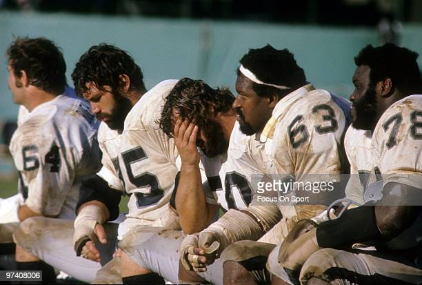 CIRCA 1970's Offensive tackle John Vella centre Dave Dalby with their heads down as teammates Art Shell guard Gene Upshaw of the Oakland Raiders...