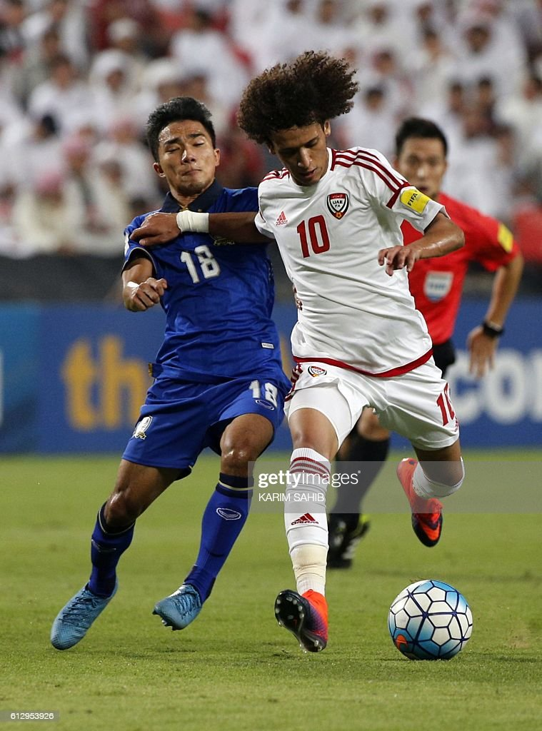 UAE's Omar Abdulrahman (R) dribbles by Thailand's Chanathip Songkrasin during the 2018 FIFA World Cup Qualifiers match between United Arab Emirates and Thailand at the Mohammed Bin Zayed Stadium in Abu Dhabi on October 6, 2016. / AFP / KARIM