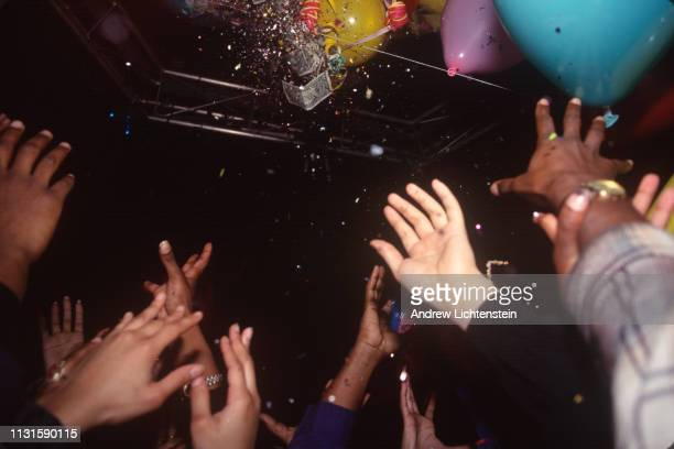 NEW YORK NY CIRCA 1990's people party at a nightclub as money drops from a crystal ball to celebrate New Year's eve n the 1990's in New York City