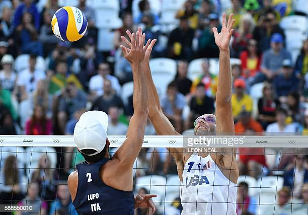 USA's Phil Dalhausser tries to block the ball in front of Italy's Daniele Lupo during the men's beach volleyball qualifying match between USA and...