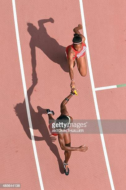 USA's Phyllis Francis hands the baton to USA's Jessica Beard in the qualifying round of the women's 4x400 metres relay athletics event at the 2015...