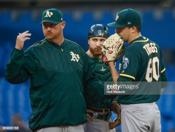 A's pitching coach Scott Emerson calls for the trainer after Oakland Athletics starting pitcher Andrew Triggs had a problem on the mound He came out...
