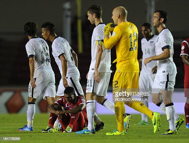 USA's players leave the field as a Panamanian player sits in dejection in the end of their Brazil 2014 FIFA World Cup Concacaf qualifier match...