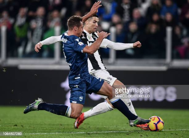 SPAL's Polish defender Thiago Rangel Cionek and Juventus' Portuguese forward Cristiano Ronaldo go for the ball during the Italian Serie A football...