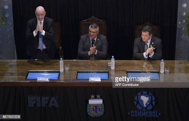 FIFA's President Gianni Infantino gestures next to AFA's President Claudio Tapia and CONMEBOL's President Alejandro Dominguez at Argentine Football...