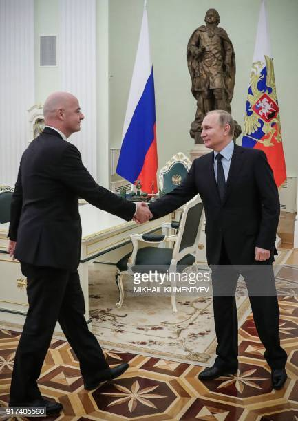 FIFA's president Gianni Infantino shakes hands with Russian President Vladimir Putin during their meeting in the Kremlin in Moscow on February 12...