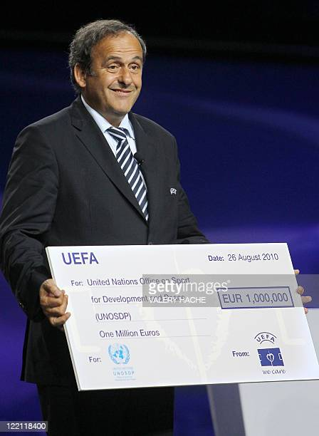 UEFA's president Michel Platini stands on stage showing a giant € 1 million check for the United Nations Office on Sport for Development and Peace at...