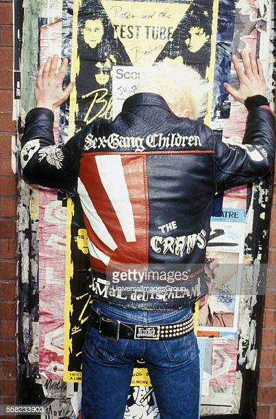 80's Punk standing facing flypostered wall wearing 'Cramps' leather jacket Kings Road London 1980's