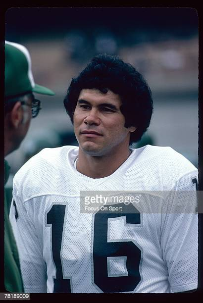 CIRCA 1980's Quarterback Jim Plunkett of the Los Angeles Raiders is talking to a coach on the sidelines during an early circa 1980's NFL football...