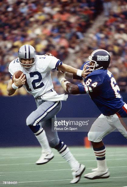 RUTHERFORD NJ CIRCA 1970's Quarterback Roger Staubach of Dallas Cowboys tries to escape the grasp of a New York Giants defender during a mid circa...