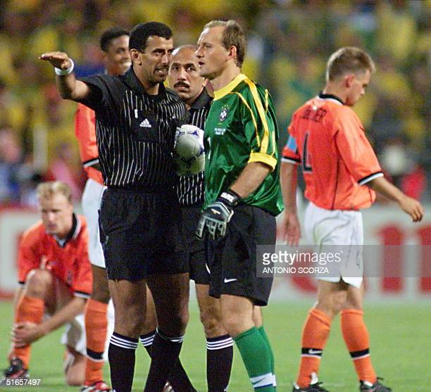 UAE's referee Ali Mohamed Bujsaim gestures as he speaks to Brazilian goalkeeper Taffarel prior a penalty shot by Dutch Phillip Cocu at the end of the...