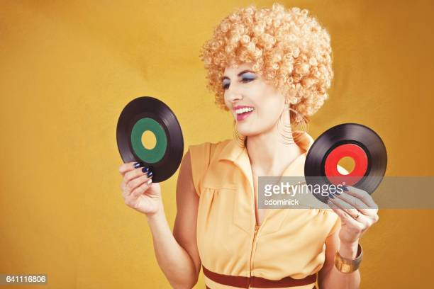 70's retro woman holding records - permed hair stock photos and pictures