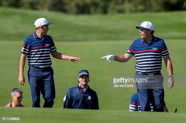 USA's Rickie Fowler and Phil Mickelson gesture as they walk up the fairway with ViceCaptain Bubba Watson during a practice round ahead of the 41st...
