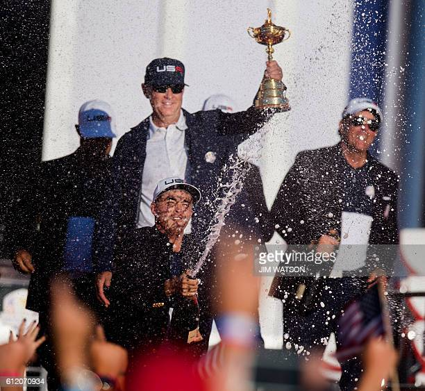 USA's Rickie Fowler's sprays champagne as Captain Davis Love III holds up the trophy as they celebrate winning the 41st Ryder Cup at Hazeltine...
