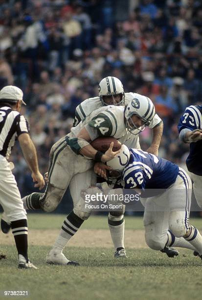 BALTIMORE MD CIRCA 1970's Running back John Riggins of the New York Jets carries the ball and is hit by linebacker Mike Curtis of the Baltimore Colts...