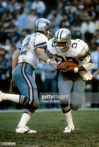 Running back Tony Dorsett of the Dallas Cowboys in action takes the hand-off from quarterback Roger Staubach circa late 1970's during an NFL game....