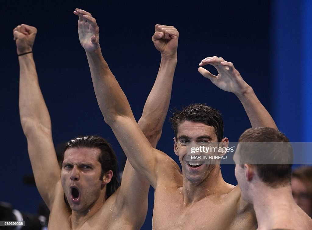 TOPSHOT - USA's Ryan Murphy (R), Cody Miller, Michael Phelps (C) celebrate after the Men's swimming 4 x 100m Medley Relay Final at the Rio 2016 Olympic Games at the Olympic Aquatics Stadium in Rio de Janeiro on August 13, 2016. / AFP / Martin BUREAU