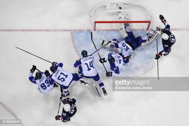 S Ryan Stoa watches as Slovakia's Jan Laco and other Slovakia players defend their goal in the men's preliminary round ice hockey match between the...