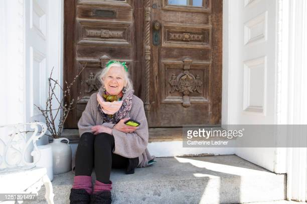 50's scandinavian woman sitting, holding phone on old granite step with ornate wood door in background - catherine ledner stock pictures, royalty-free photos & images