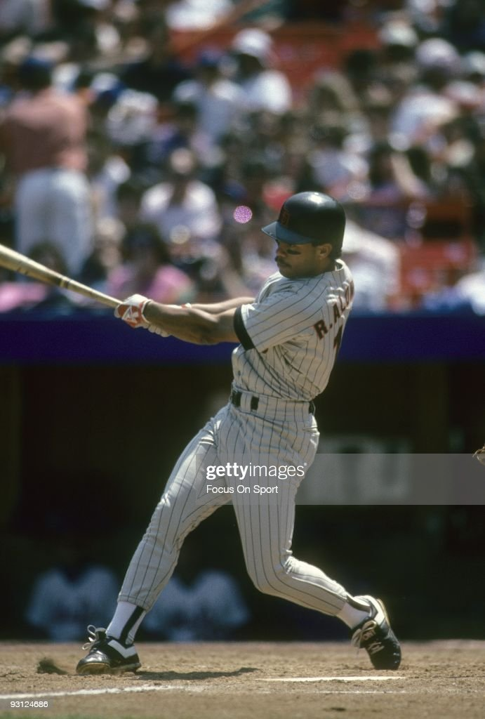 FLUSHING, NY - CIRCA 1980's: Second baseman Roberto Alomar of the San Diego Padres swings and watches the flight of his ball against the New York Mets during a circa late 1980's Major League Baseball game at Shea Stadium in Flushing, New York. Alomar played for the Padres from 1988-90.