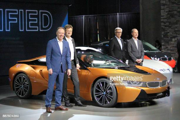 BMW AG's senior management stand next to the company's new BMW i8 Roadster unveiled at the Los Angeles auto show at the LA Convention Center in...