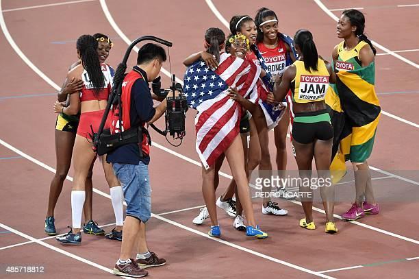 USA's silver medal winning relay team Allyson Felix Jasmine Todd English Gardner and Jenna Prandini embrace members of Jamaica's gold medal winning...