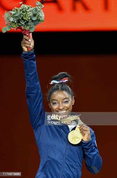 USA's Simone Biles poses on the podium during the medals ceremony of the womens allaround final at the FIG Artistic Gymnastics World Championships at...