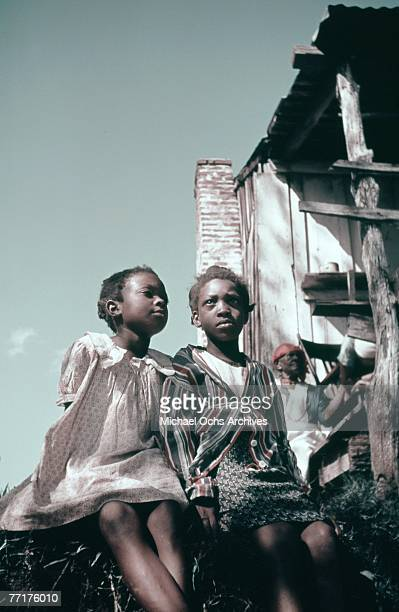 MID 1930's Slave children sit outside their house during a recreation of pre Civil War life on a plantation circa mid 1930's in the deep south