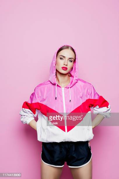 80's style portrait of beautiful woman in oversized tracksuit against pink background - sports clothing stock pictures, royalty-free photos & images