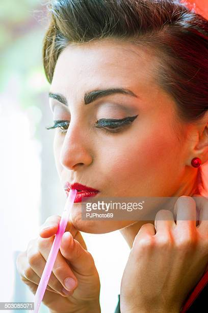 1950's Style - Portrait of beautiful woman using drinking straw
